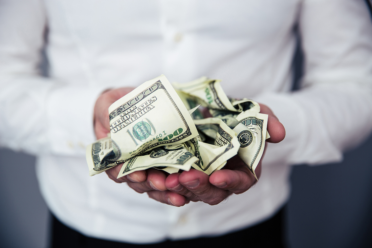 Closeup image of a business man hands holding money bills of US dollar